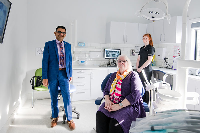 dentist with patient and dental assistant in surgery room
